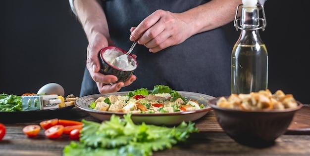 Шеф-повар заправляет салат цезарь специальным свежим соусом