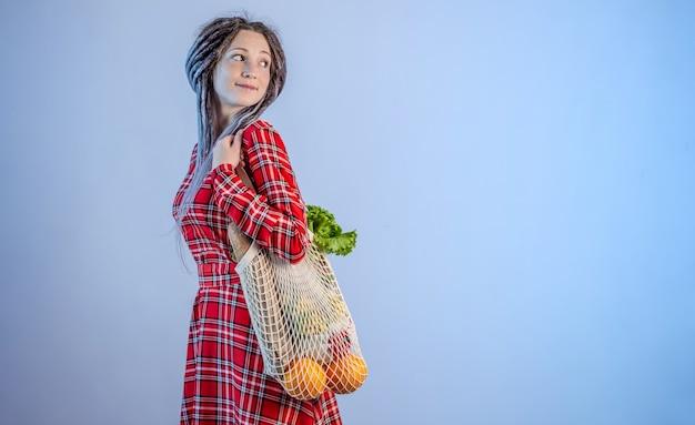 ストリングバッグにアイテムを運ぶ女性
