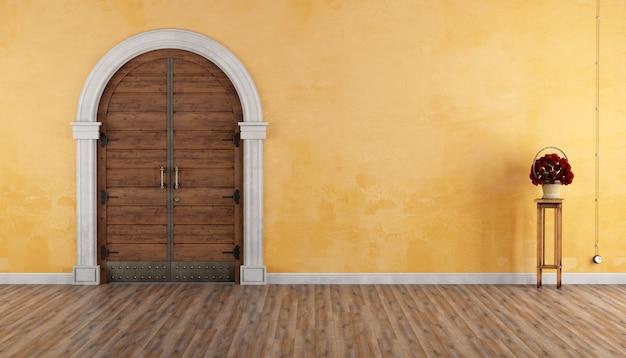 Домашний вход со старым порталом и деревянной дверью