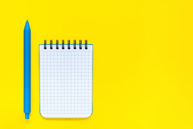青いペンと黄色のメモ帳を開く