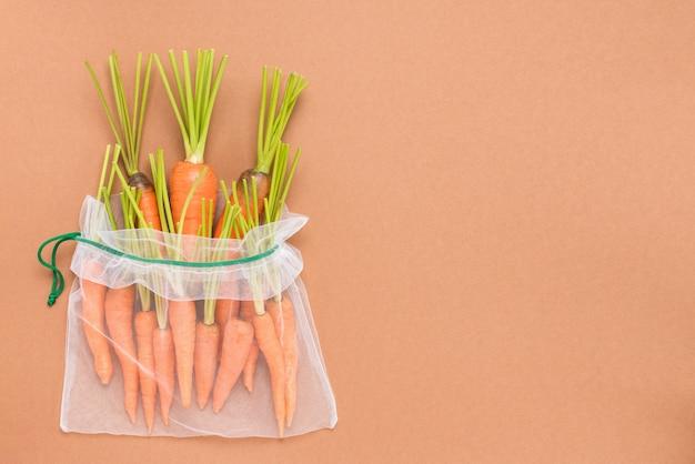 再利用可能な環境に優しいメッシュバッグに入った新鮮で熟したジューシーなニンジン。