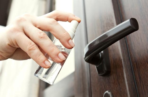 Женщина наносит дезинфицирующее средство на дверную ручку