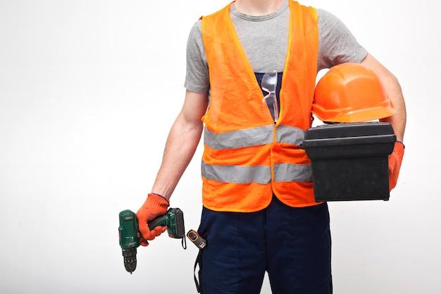 灰色の背景に手でツールボックスとプロの制服を着た労働者