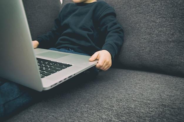子供はラップトップを保持しているソファに座っているし、漫画を見る