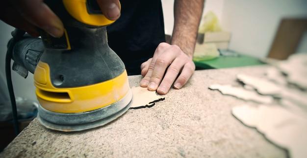 男は研磨機で木材を処理しています