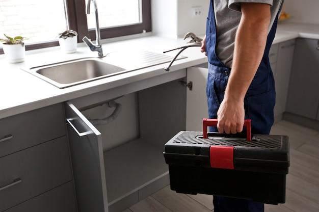 修理業者は、キッチンのいくつかの問題を修正するために顧客に来ました