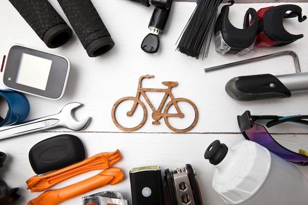小さな自転車のアイコンの周りの木製のテーブルの上に横たわるさまざまな自転車アクセサリーがたくさん