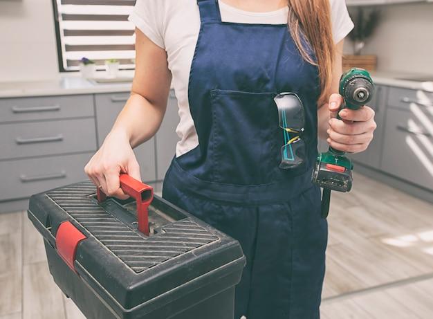 Женщина-ремонтник, одетая в рабочую форму в доме с ящиком для инструментов и другим оборудованием в руке