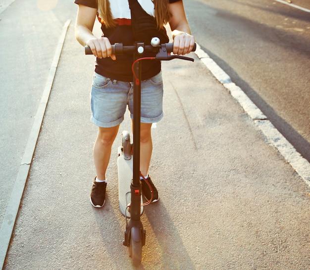 若い女性は、経路によって夜の街を通って電動スクーターに乗っています。