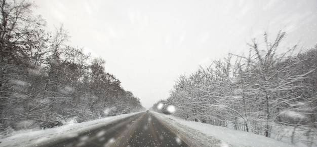 冬のアスファルト道路と外の雪の天気