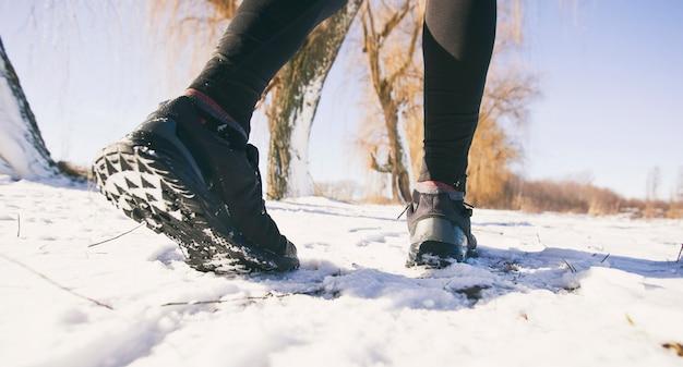 Ноги бегают по зимней проселочной дороге в снегу