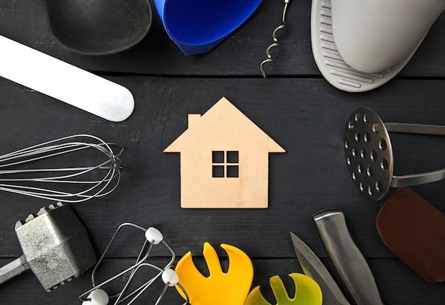 様々な台所用品とその間の小さな木造家屋