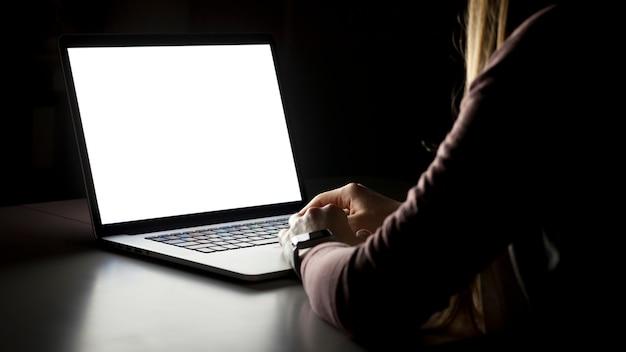 暗いリビングルームに座っているとラップトップに取り組んでいる若い女性