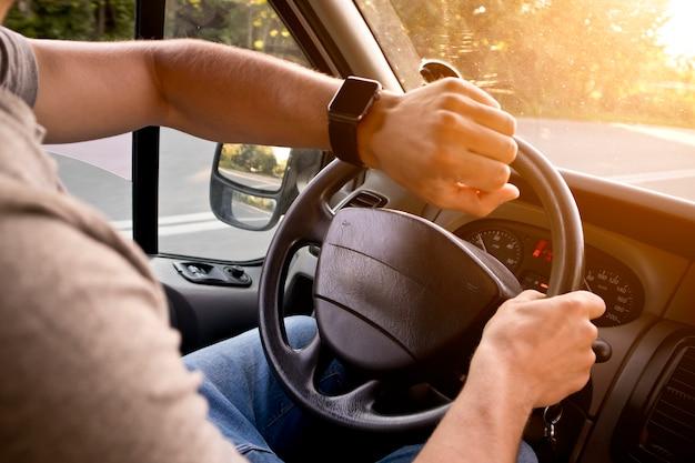 現代の車に座っている彼の手で彼のスマートウォッチを探している若い男
