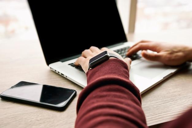 Молодой человек работает на своем ноутбуке