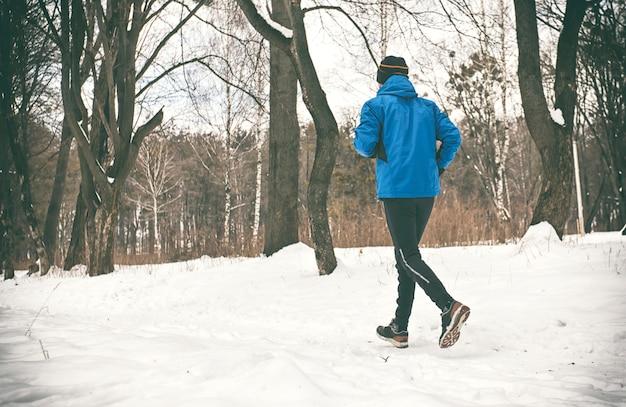若い男は冬の公園でジョギングします。