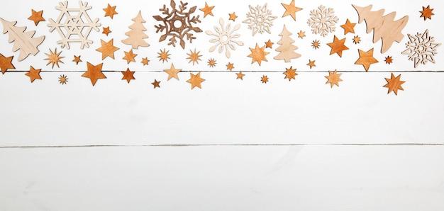 白い木製の机の上の小さな木製の装飾がたくさんある美しいクリスマスの背景。