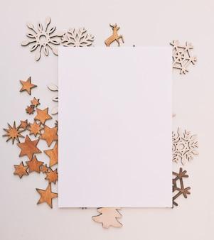 白い机の上の小さな木製の装飾がたくさんある美しいクリスマスの背景。