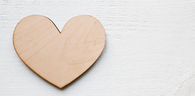 白いテーブルの上の木の心。バレンタインコンセプトの背景