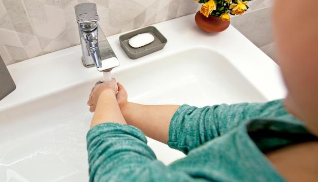 少年は水の下で石鹸で手を洗っています