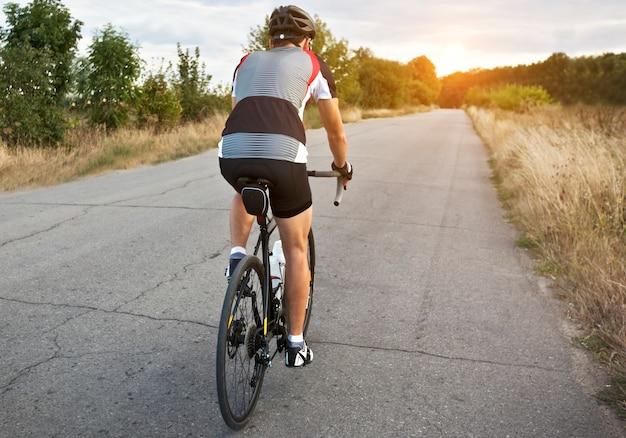 サイクリストはアスファルト道路で街の外の彼のロードバイクでトレーニングしています