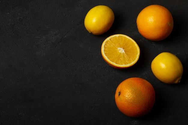 Апельсины и лимоны на темном бетонном фоне