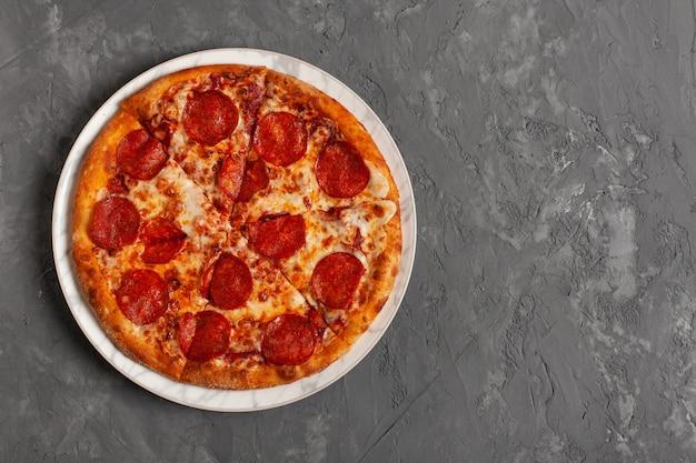 Пицца пепперони на сером фоне бетона с копией пространства. взгляд сверху отрезанной пиццы пепперони.