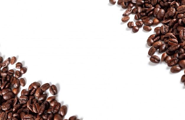 Предпосылка кофейных зерен изолированная на белой предпосылке с космосом. вид сверху.