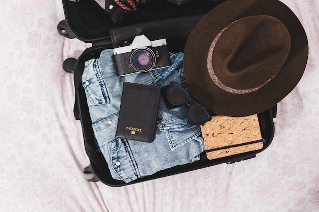 Открытый чемодан с одеждой и аксессуарами для путешествий