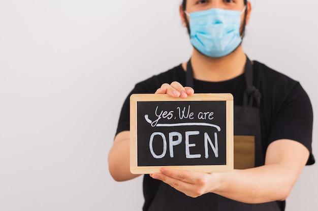 笑顔の人が「はい、オープンです」という看板を掲げています