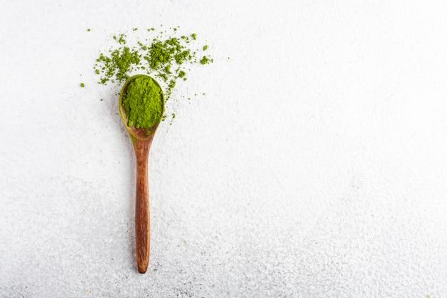 白い背景の上の抹茶茶粉末と木のスプーン