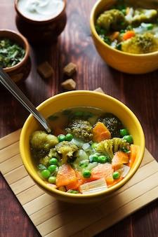 Вертикальное фото овощного супа с морковью, зеленым горошком и брокколи