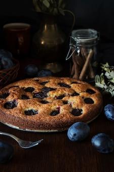 シナモンとプラムのケーキの暗い写真
