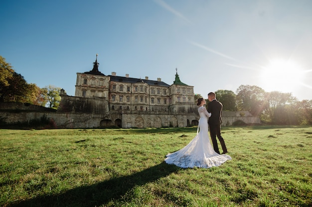 古い城の近くの日光の下を歩く素敵な結婚式のカップル