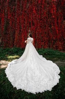 Невеста в красивом свадебном платье с длинным шлейфом на природе