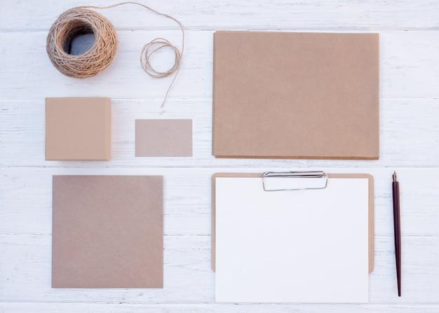空の別のアイテム、ギフト用のボックスのセットをクラフト、封筒、カード、シート、木製の背景にロープ