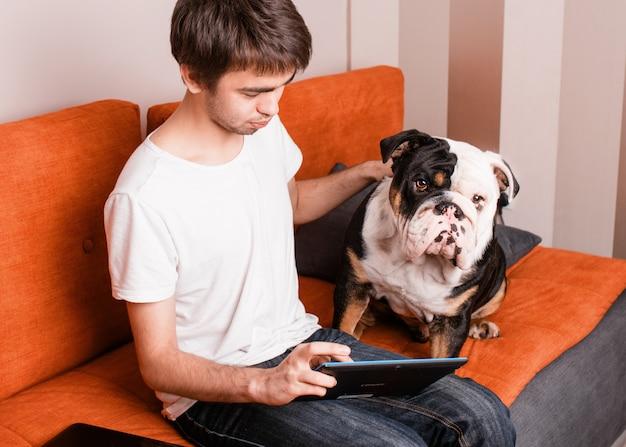 彼の白と黒の犬と一緒にタブレットでオンラインで勉強または学習しているソファーに座っている一人の少年