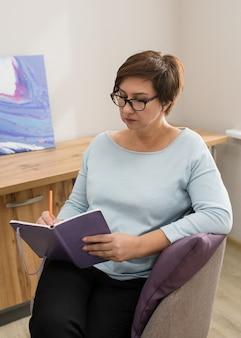 座っているとオフィスのメモ帳でメモを作っている女性
