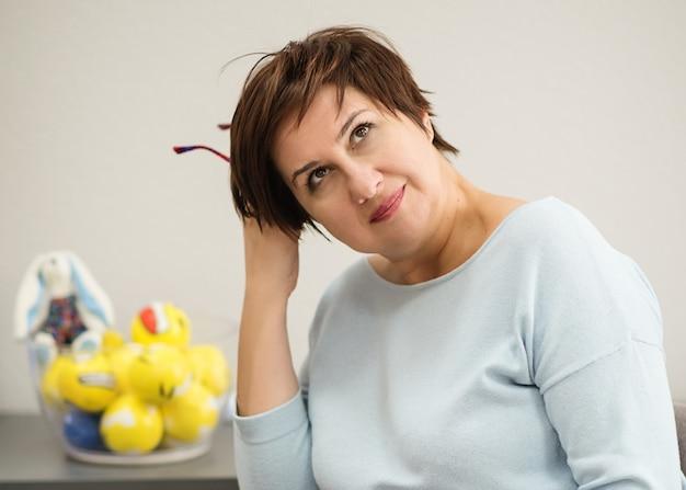 笑みを浮かべて、考えて、オフィスに座っている女性心理学者