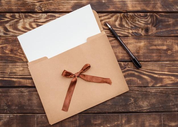 クラフト封筒、それにホワイトペーパー、古い茶色の木製のテーブルに黒の鉛筆