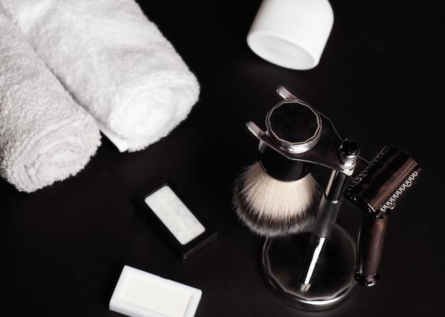かみそり、ブラシ、黒の背景に香水。