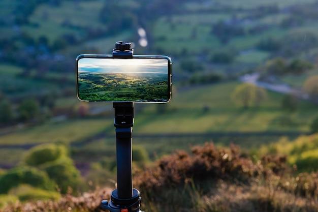 ヨークシャーの通常の田舎のイングランドの風景の写真を撮る三脚に電話