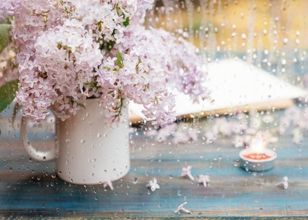Чашка с сиренью, свеча и конверт на старинные деревянные поверхности в весенний дождь день