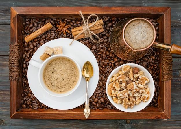Чашка кофе, орехи в миске, кофейник, корица, анис, сахар, кофейные бобы на деревянном подносе