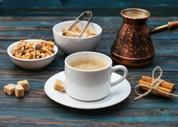 Чашка кофе, орехи в миске, кофейник, корица, сахар на деревянном фоне