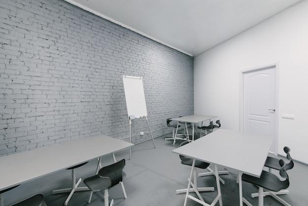 明るくスタイリッシュなオフィスの部屋。オフィスの灰色のインテリア。最小限の作業スペース