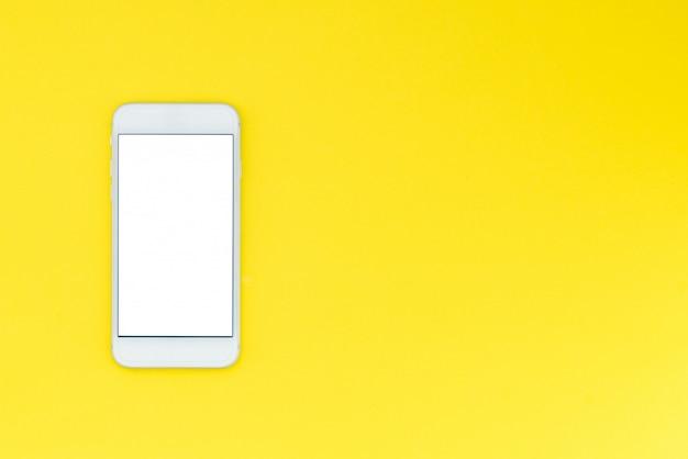 黄色の背景に白のモダンなスマートフォン。フラットレイ