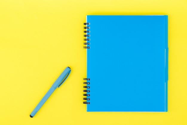 Голубая тетрадь с ручкой на желтой предпосылке. плоский шаблон. место для текста.