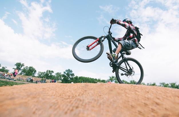 Молодой человек делает трюки на горном велосипеде. велосипедист прыгает на велосипеде.