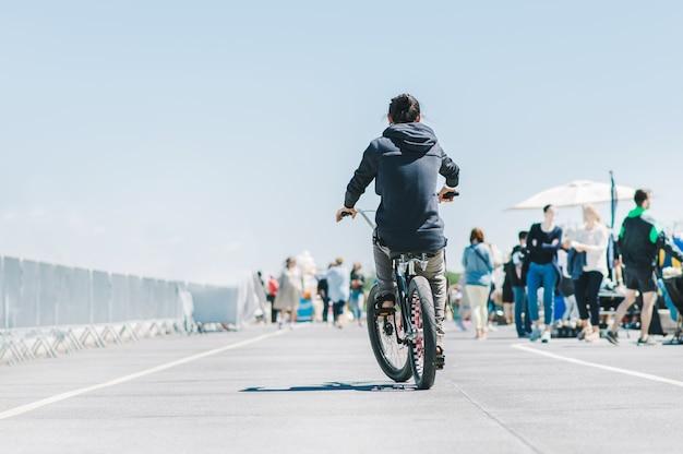 サイクリストの後ろ。自転車でアスファルトに乗る男性。後ろから自転車に乗る